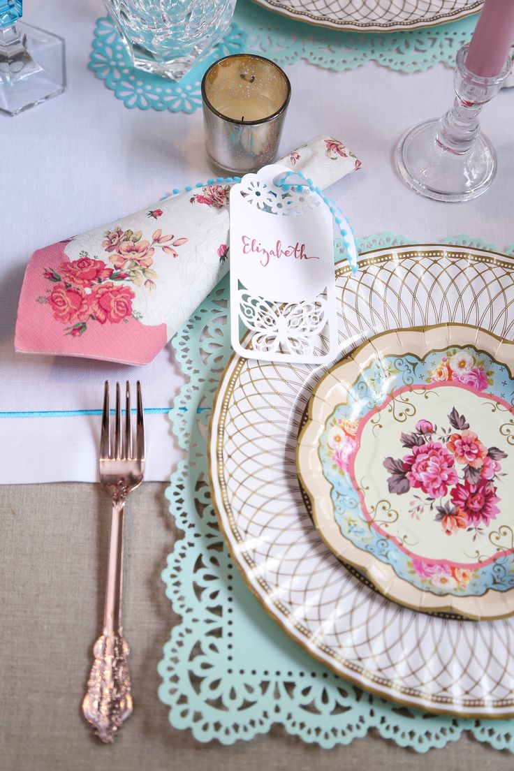 china printed paper plate and charger with floral printed paper napkin wrapped in ribbon and paper place card with rose gold plastic cutlery