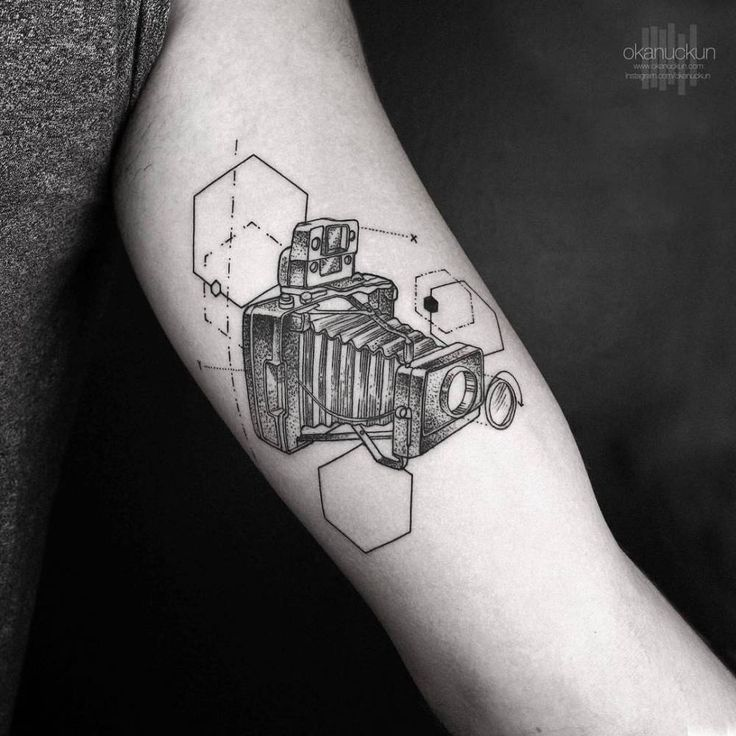 Vintage camera tattoo on the left inner arm.