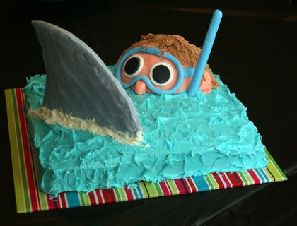 I saw this design somewhere else, Family Fun magazine, I think. It was really easy and perfect for my son's shark birthday. The shark fin is cut out of a cookie and coated in royal icing. The head is half of the ball cake pan and covered in fondant.