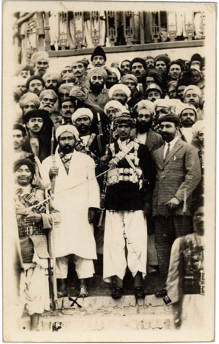Photograph of Bacha i Saqao (Habibullah Kalakani) standing in a white costume in a large party of Afghan men, some armed, standing on a stairway. Said to be a wedding party.