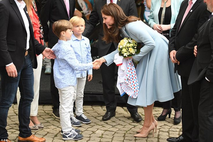 Kate received a bouquet from two very smartly dressed boys in matching outfits as she arrived at a cycling themed festival in Place de Clairefontaine