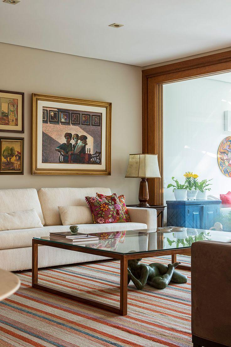 Decoração com personalidade, decoração colorida de sala de estar com obras de arte, tapete, almofada estampada e com sofá branco.