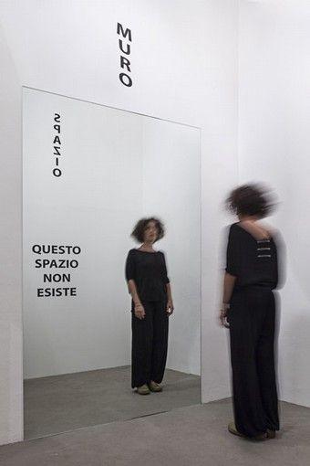 """Michelangelo Pistoletto, """"Questo spazio non esiste"""", 1976. Specchio, lettere in vinile adesivo, dimensioni ambiente. Opera n°70 dal libro giallo 'Cento mostre nel mese di ottobre', Torino 1976"""