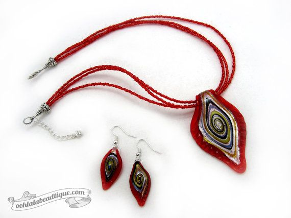 Complete the look every season by adorning this Red Murano glass jewelry set. The gorgeous color palette of this jewelry set has a chic appeal and rich dazzle compliments every ensemble! MATERIAL: Red Murano glass leaf shaped pendant with silver foil and swirl pattern, Siam red foiled Czech glass seed beads, and Tibet silver are combined together for a stylish look. The necklace is strung onto tigers tail wire for strength, durability and drape. Finished off with a large lobster clasp and a…