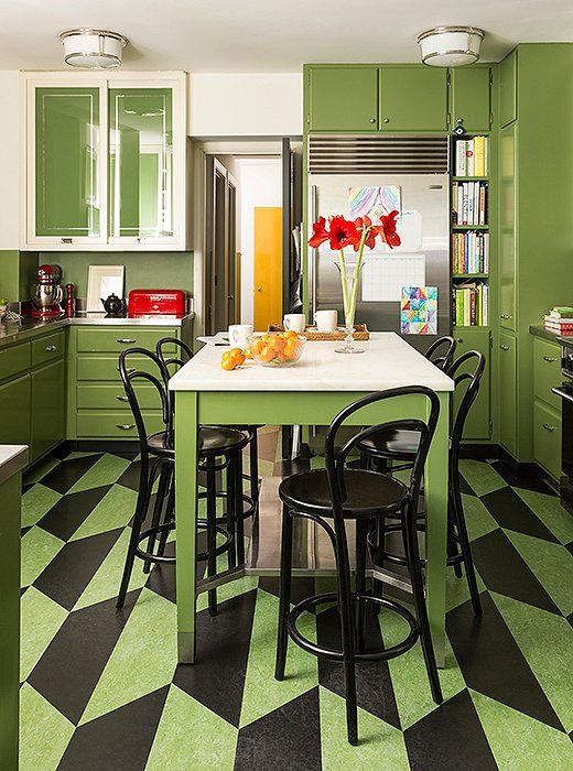 """EnsconcedinBenjamin Moore's Courtyard Green, the kitchen is as stylish as it is practical. The glass cabinet doors were reverse-painted to keep messy shelves out of sight but still reflect incoming sunlight. The linoleum floor provides a pop of pattern,feels good under foot, and iseasy to clean.Kate's favorite element, though, is the marble island: """"I like the way it looks as itstains and gets worn… it acquires a kind of personality."""""""