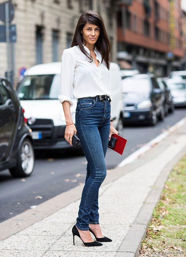 Barbara Martelo posa para foto de street style no meio dos carros usando calça jeans skinny de cintura alta, cinto preto com fivela prata, camisa branca meio aberta e scarpin preto