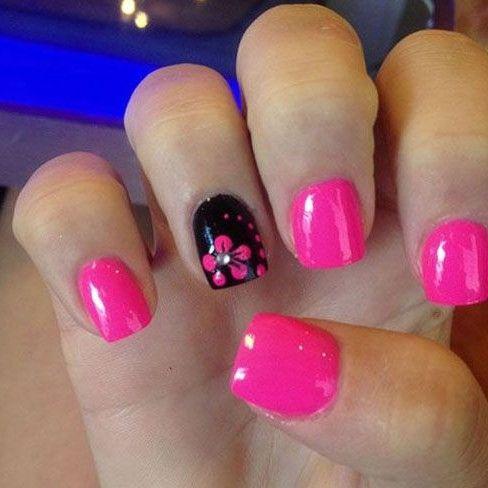Hermosas uñas en rosa fucsia, una de ellas en negro brillante decoradas con una flor con una perla y una línea curva de lunares