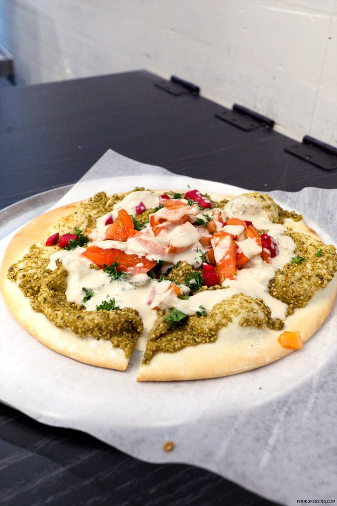 Falafel Flatbread featuring falafel mix, spread and baked on house-made flatbread. It was topped with tahini sauce, tomatoes, pickled turnip and parsley