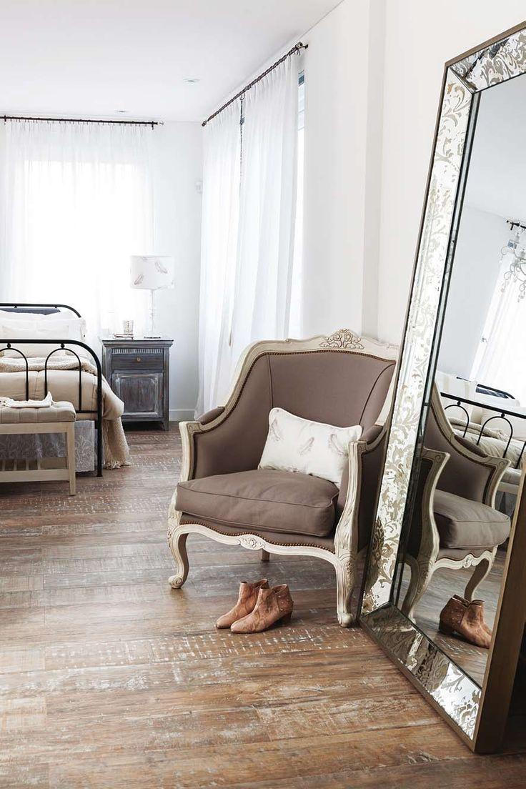 Estilo aireado, playero y elegante en la ciudad: vestidor integrado a la habitación, con gran espejo de marco trabajado, sillón marrón y piso de madera rústica.