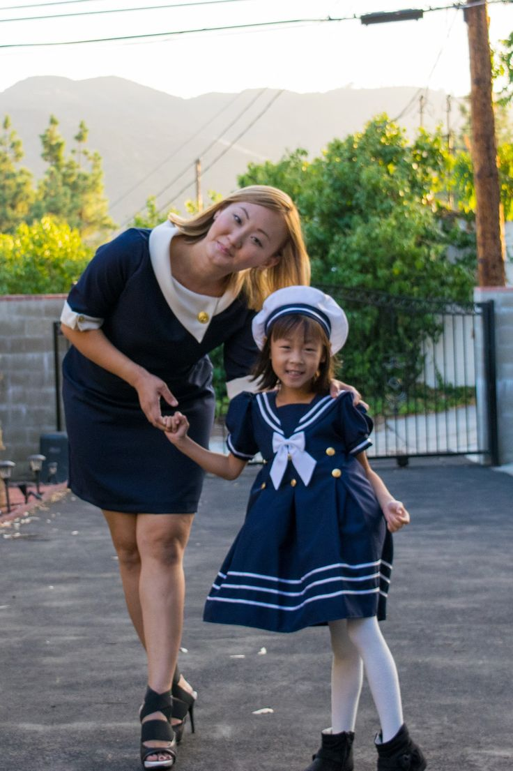 Elegant retro mod dress with signature nautical navy and off-white contrast. Featuring scarf neckline, 3/4 sleeves with folded cuff. Neat gathering on the left waistline, cleverly designed to embrace your body curve. Gold tone anchor buttons complete this Mommy and Me nautical trend look!