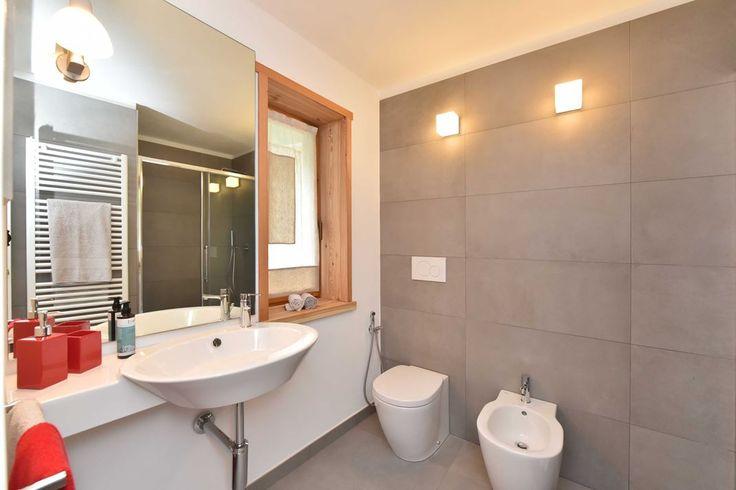 Sulla parete in piastrelle del bagno sono stati applicati dei cubi in vetro a luce diffusa di Leucos, sullo specchio invece una lampada orientabile di Rotaliana.