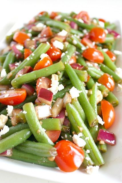Balsamic Green Bean Salad.  Fresh bright green beans with splashes of red tomato, purple onion, and white feta.  Crunchy tender green beans are marinated in a garlic-balsamic dressing with a hint of lemon.