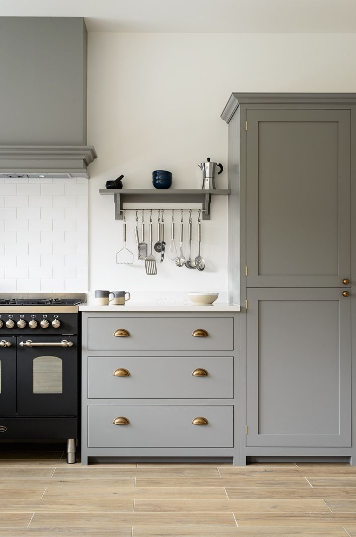 Beautiful deVOL Shaker cabinets painted in 'Lead', classic brass door furniture, a lovely black Britannia range cooker and beautiful Aged Oak Porcelain flooring by our sister company /floorsofstone/