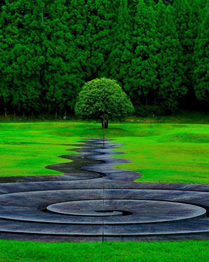 絶景にロマンを求めて① ・ 仕事がようやく一段落 エアーポケットのように 空いた一週間 絶景を求めて 京都、大阪、奈良、滋賀を ぶらぶらしました。 ・ 【1日目】 張り切って早起きして向かったのは 奈良県宇陀市の「室生山上公園芸術の森」。 世界的に有名な彫刻家ダニ・カラヴァンが 設計したアートでシュールな公園です。 駐車場に辿り着くと 車が1台しか停まってない 営業しているのかと不安になってきた・・ 施設に入ると暇を持て余している 職員さんがお出迎え ホッと一安心。 早速、お目当ての「螺旋の水路」へGO! 波打つ水路が木へと向かっている 不思議なモニュメントは 古代から太陽を信仰していた 室生という大地から インスピレーションを受けたそうです。 伊勢神宮へ繋がる太陽の道と 思えばこのシュールなモニュメントも 理解できないこともない? いや、僕には分かりませんでした(笑) このモニュメントを写真に収めようと 夢中でシャッターを切っていると ぽつぽつと雨が お約束のように土砂降りに(泣) どうやら旅行から帰ってきた後も 水難の相が出ているみたいだ。 とほほ・・…