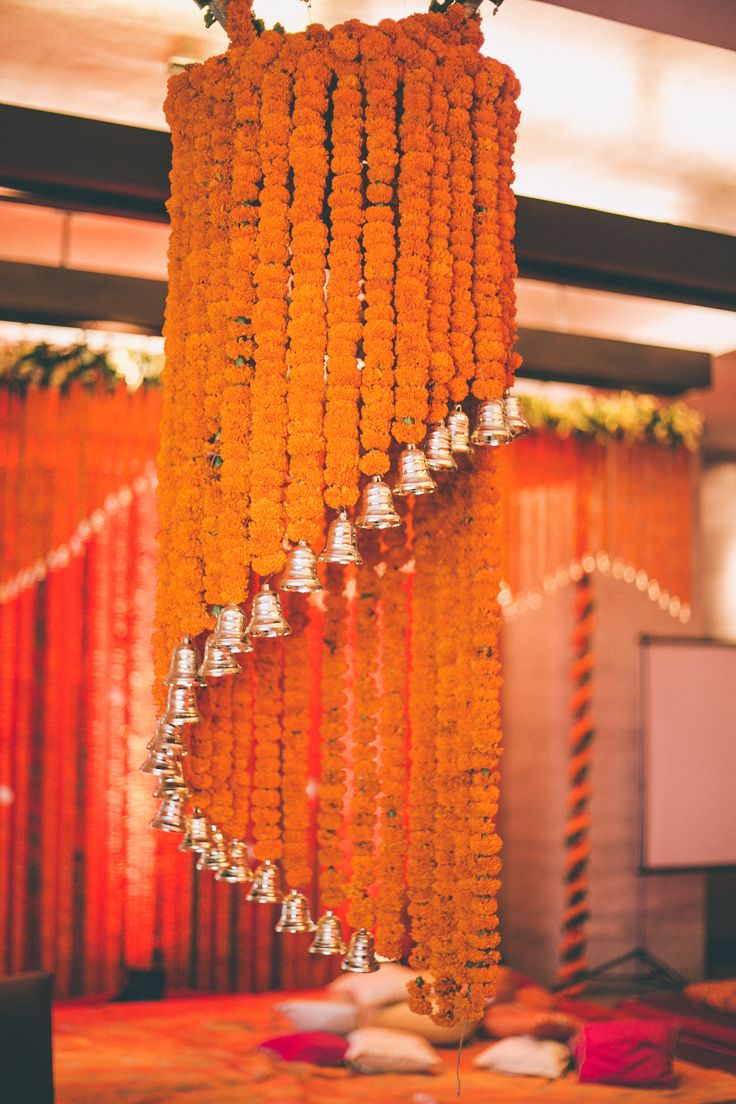 Floral chandelier made of orange marigold and bells - perfect add-on to your Mehendi decor!