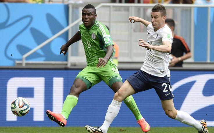 Nigeria's Emmanuel Emenike attempts a shot at goal against the Arsenal player Laurent Koscielny for France