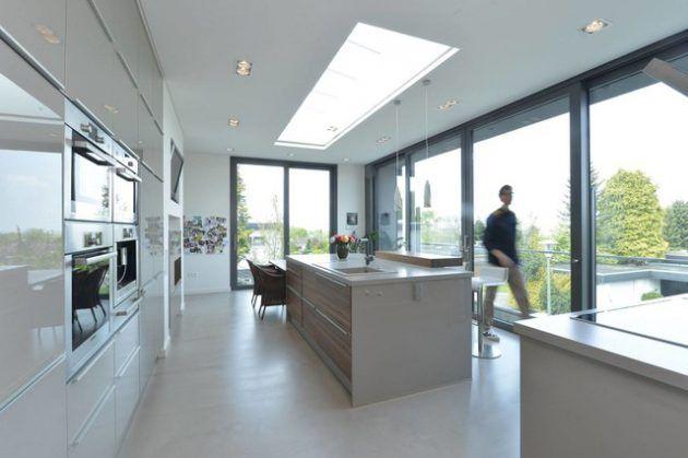 fenêtre de toit de style verrière dans une cuisine de style moderne avec ilot central et table de repas