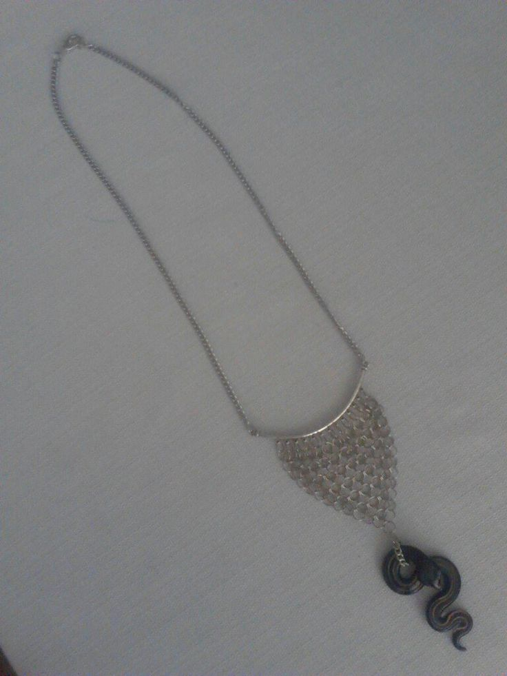 A snake pendant atatched to nickel plated chain maille rings, on a bail that is on a chain with a lobster claw clasp. Sold