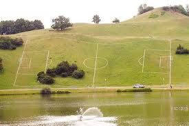 Some hilly field - Somewhere  Situated at a 45 degree incline next to a lake with the added inconvenience of some trees in the middle of the pitch our last entrant wins the 'Most Awkward Pitch to Play Football On' Award.