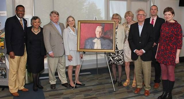 Johnson C. Smith University president Ronald Carter, left, with Biddle descendants and a portrait of benefactor Mary Biddle at the university's 150th anniversary celebration.