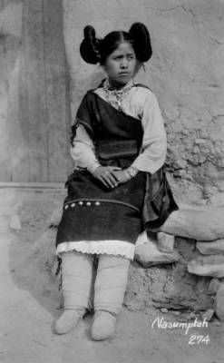 Nasumptah, a Native American (Hopi) girl, poses outdoors probably in Arizona. She wears wrapped boot moccasins, dress, manta, beaded necklaces, and her hair in side whorls.