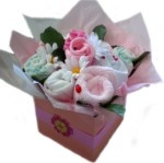 Dusk Pink Baby Bouquet - 2x disposable nappies, 2x facewashers, 2 singlets, 2x pairs of socks, 1x short sleeve all-in-one and 1x bib.