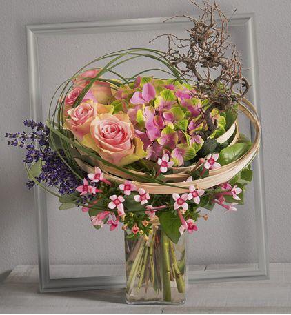 Arabesque: Bouquet fantaisie de roses roses et fleurs variées violettes et roses avec travail de branchage structuré