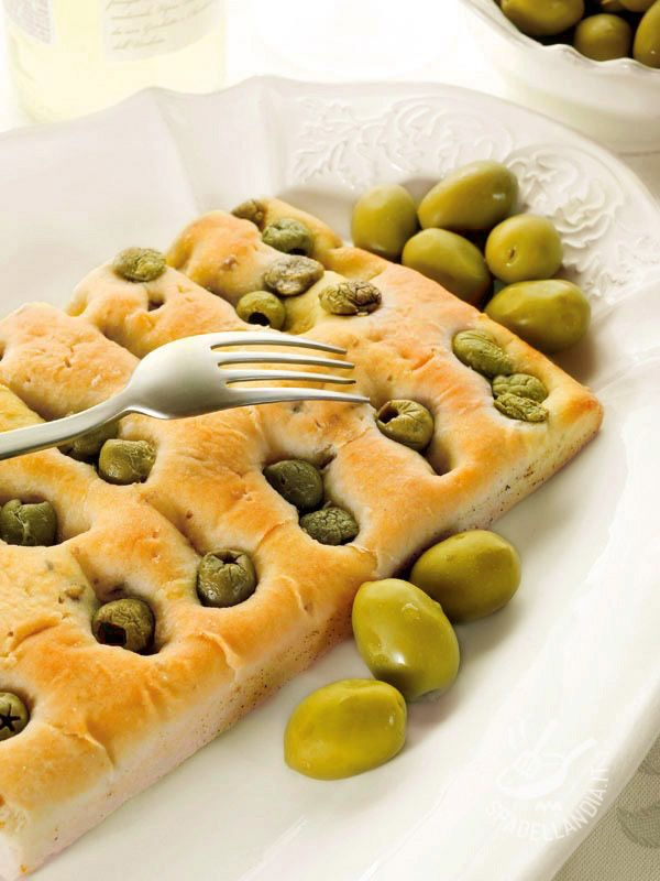 La Focaccia genovese alle olive verdi è perfetta anche come semplice e genuino finger food (cibo da spilluzzicare), tagliata in golosi quadratini!