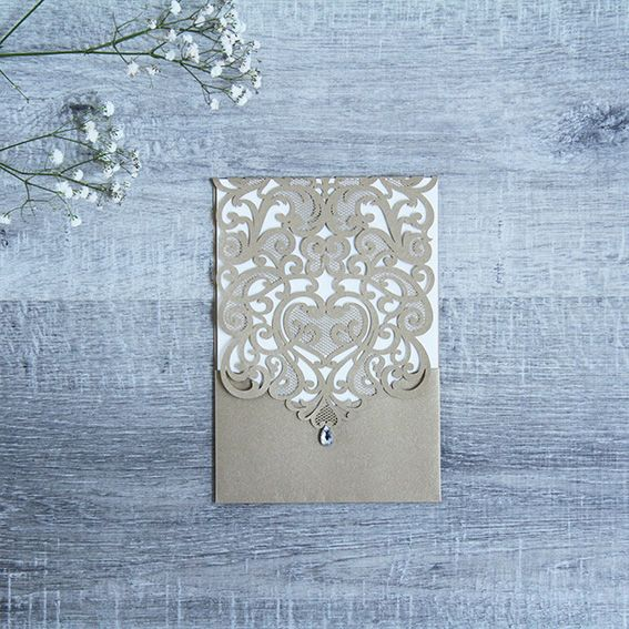 Gold Everesence Invitations This invitation has beautifully laser cut swirls ending with a teardrop crystal over a folded card. This beautiful style adds a little sparkle to your invite, perfect for a glamorous wedding! Available in a Gold or White pearl finish.