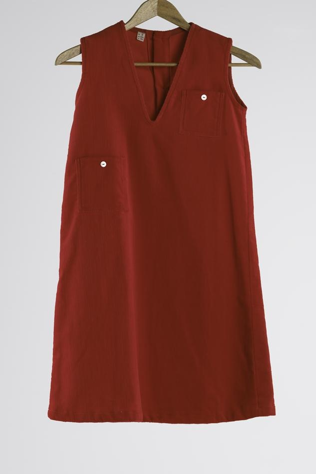 Red corduroy pinafore worn by young female patients at St Nicholas Hospital, a hospital for children with intellectual disabilities, in Carlton, Victoria, Australia, circa 1980. It was manufactured by Branch Central Clothing and designed by Elsie Storr. Some of the needle work mending on the dress may have been undertaken as part of an occupational therapy program. Collection: Museum Victoria