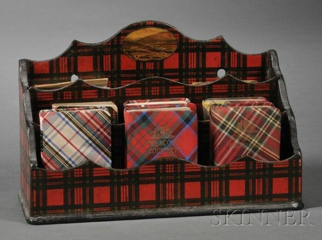"""Victorian Tartanware Letter Rack with Eight Miniature Tartan Books, the papier-mache rack with three compartments with ogee top edges, center of back applied with a small roundel print of a Highlands view, ht. 6 1/2, wd. 10, dp. 4, with seven fabric-covered miniature books (six """"Thistle Library""""), and one boards, late 19th/early 20th century, all Scottish subjects. Would look sensational on a writing desk."""