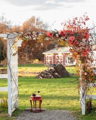 A white arbor acted as a chuppah for this Jewish ceremony, wrapped with branches, roses, and persimmons. See more of this fall outdoor wedding in the Hudson Valley on our website!
