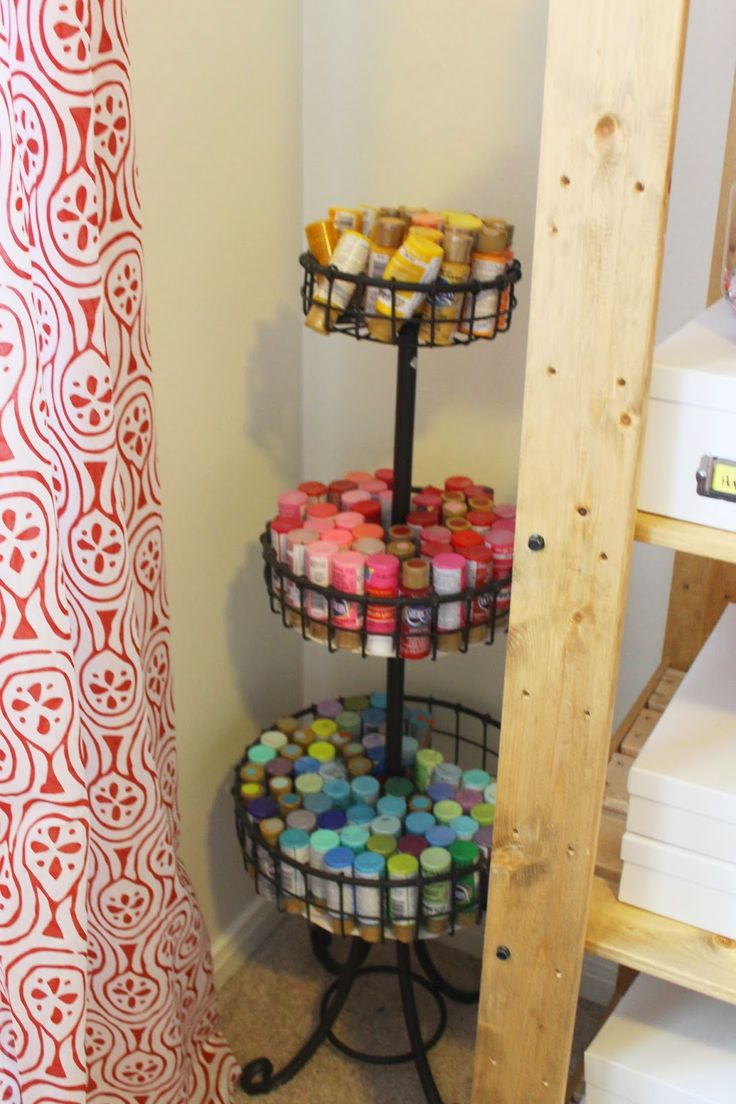 Great craft room space. Acrylic paint tubes get the perfect home in this tiered basket. Group by color, and all flipped upside down, they are easy to find, and pretty to look at! Lots of open shelving, perfect for displaying a collection of craft items, or collectables.  Simple and cheap ikea shelving!   Theraggedwren.blogspot.com