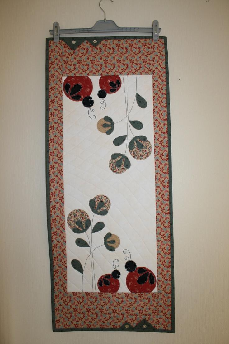 Løper med applikert blomst og marihøne.    Måler 42 x 103 cm.