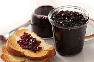 Bottled grape juice, sugar and fruit pectin are cooked briefly then processed in a canner to produce gleaming jars of homemade jelly.