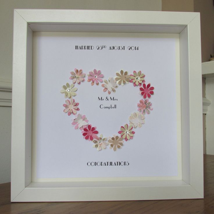 """These wonderful framed 3d artwork are a perfect gift for a wedding, a unique keepsake to be cherished. You provide your personalisation, colour choice (each design is unique, however we will colour match as closely as possible - Please specify if you would like glitter added) and the wording you require underneath or in the heart and we will do the rest. Handmade with the finest quality card and mounted in a deep box frame, these are a stunning addition to any wall. Frames measure 12"""" x…"""