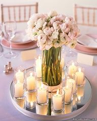 A vase of soft pink ranunculus together with shimmering votive candles on top of a mirror makes a beautiful centerpiece.