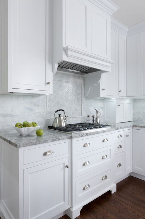 Lovely kitchen features white shaker cabinets paired with Super White Quartzite countertops and calcutta marble subway tile backsplash. White paneled kitchen hood is accented with white corbels and paired with white marble herringbone cooktop backsplash over integrated cooktop above pot and pan drawers.