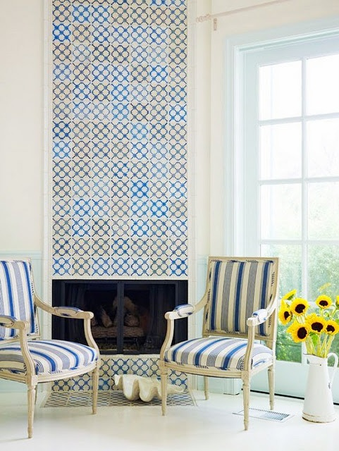 Love these Portugese tiles used as an artistic focal point above the fireplace.  This rom has a Swedish vibe to it that is modern and fresh.