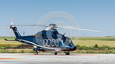 A helicopter on ground on heliport in the middle of green field. Copy space on top on clear blue sky.