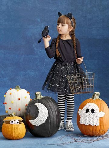Kids of all ages can glue colored pom-poms to a plain or painted pumpkin. Attach ¼- to ½-inch pom-poms to pumpkins using tacky glue (like Aileen's Original).  For a surprise, slice off the top fifth of a pumpkin, scoop out the insides, and prop it open with toothpicks in the back. Glue small black pom-poms to large white ones for eyes.  For a moon or a ghost, first paint your design with acrylic paint. Let dry, then glue on the pom-poms in a tight configuration.