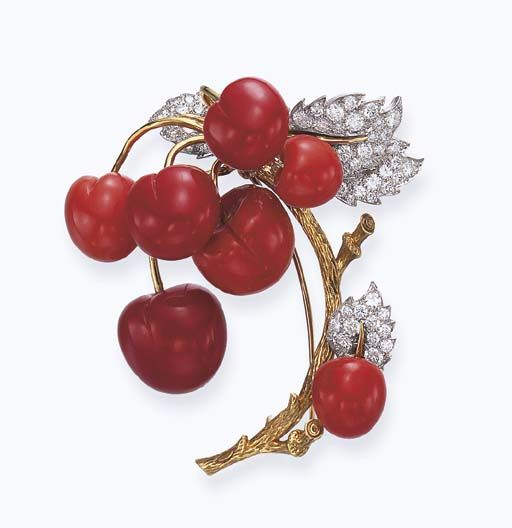 CORAL AND DIAMOND BROOCH, BY TIFFANY & CO. Designed as a gold branch suspending coral cherries, to the circular-cut diamond leaves, mounted in gold and platinum