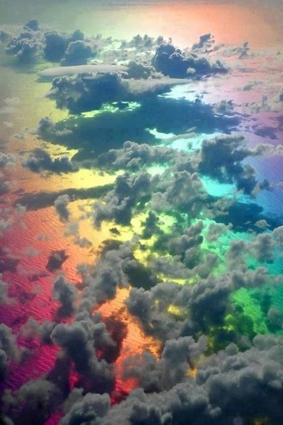 Picture taken from a plane above clouds and a rainbow.