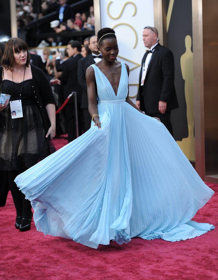 Lupita Nyong'o having fun in her Prada gown on the Oscars Red Carpet