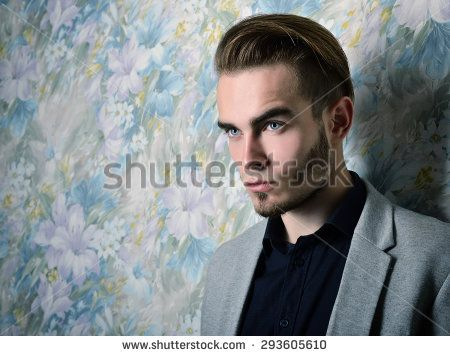 Portrait of beautiful charming young man with blue eyes and fair hair over floral background