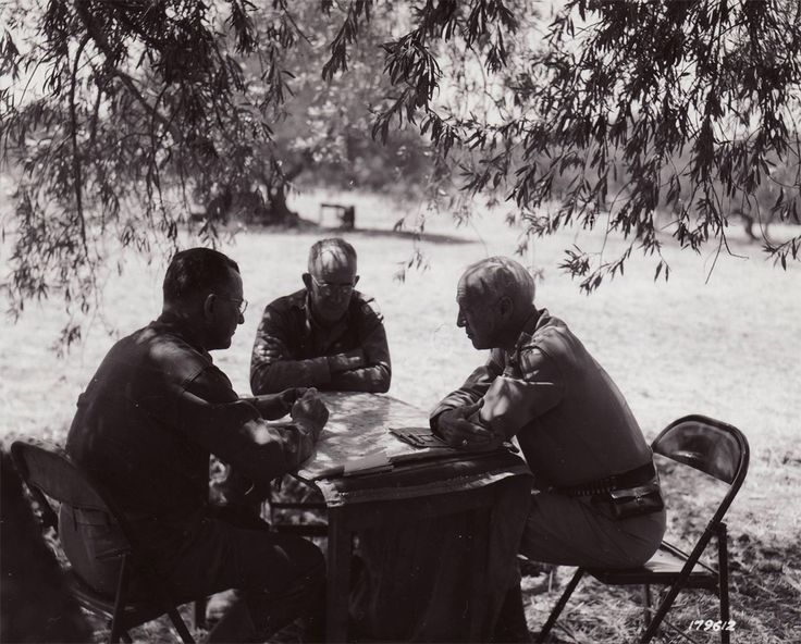 Left to right: Major General Troy H. Middleton, commander of the 45th Division; Major General Omar N. Bradley; and Patton, in a Sicilian oli...