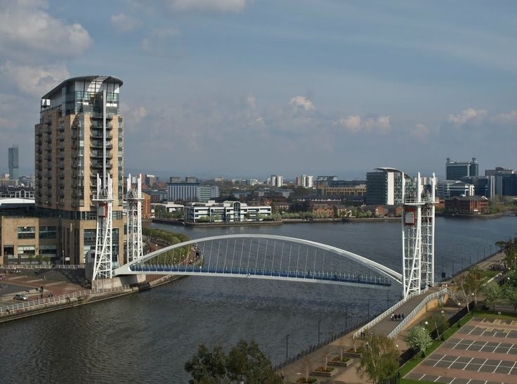"From the top of the The Imperial War Museum North, on Trafford Wharf Road, Salford Quays, Manchester, England, designed by architect Daniel Libeskind (1946), with the Millennium Lift Bridge, designed by Carlos Fernández Casad. At the left the residential tower ""Imperial Point"" and the Lowry Outlet Mall, together The Lowry Galleria, designed by DLA Design."