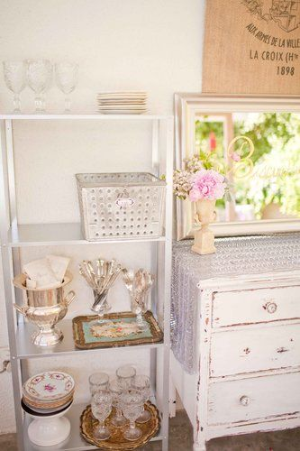 """""""We bought super, super cheap bookshelves from Ikea that flanked my little white dresser, and they ended up being a perfect complement,"""" Summer says. """"Bookshelves make great buffet pieces!"""" Source: Grey Likes Baby"""