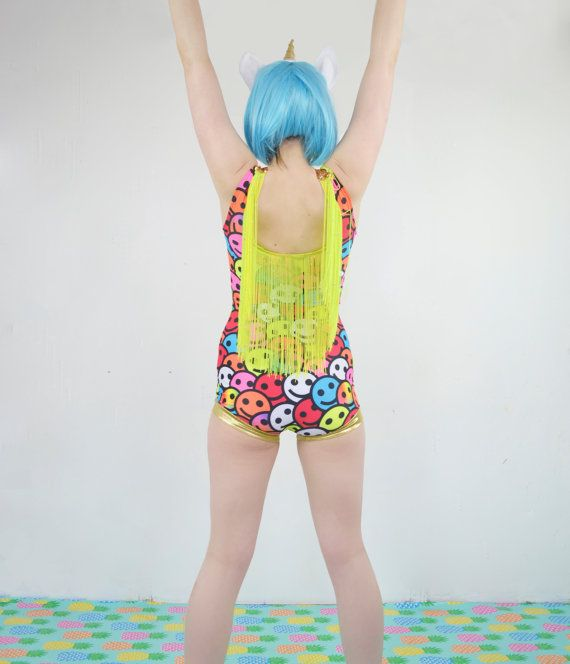 Get ready to party like its 1999! This little raver leotard is made from with super stretchy digitally printed rainbow smiley lycra. There is a flattering metallic gold velvet panel at the front, edged with shining gold sequins. The back is edged in fluorescent yellow fringing creating a fringed cape that moves about as you dance!  Each leotard is made-to-order so please provide the following measurements in inches to get a perfect fit:  - Overbust  - Underbust  - Waist (at smallest point)…