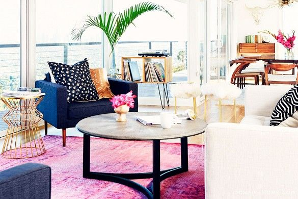 Claire Thomas of The Kitchy Kitchen's eclectic midcentury living room featuring a hot pink rug and sweeping views of Los Angeles